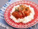 Рецепта Задушено свинско месо с доматен сос върху канапе от варен ориз